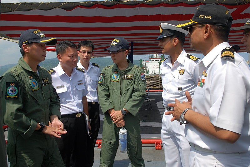 RSN and Indian Navy sailors interacting with each other during a cross-deck