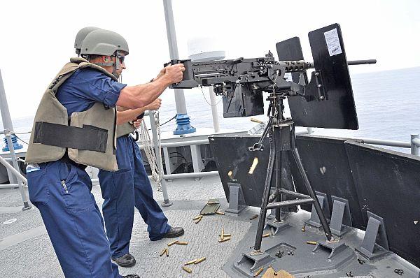Sailor fires gun on USS Rentz (FFG 46) during exercise